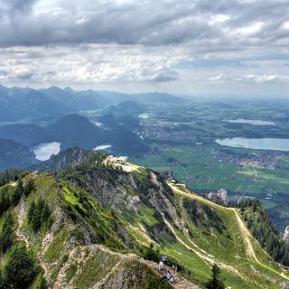 Der Tegelberg, im Hintergrund Füssen und der Forggensee, links davon die Allgäuer Alpen.