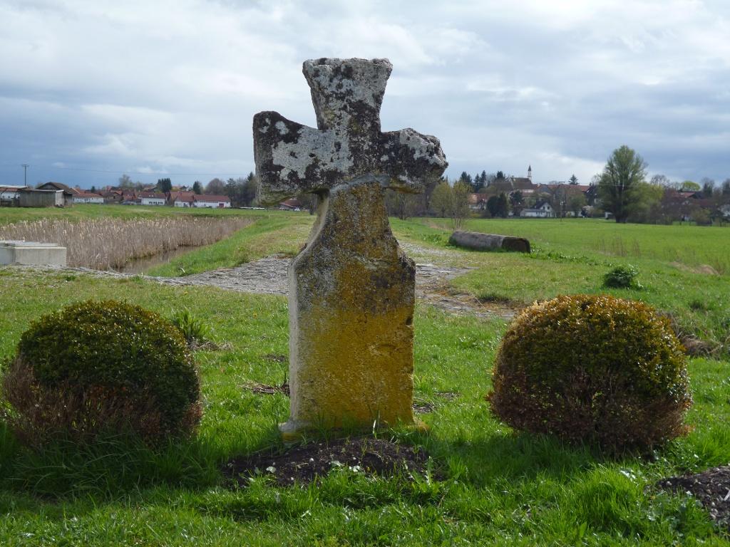 Am Straßenrand steht direkt vor dem Regenwasserrückhaltebecken ein Steinkreuz (Sühnekreuz) aus Tuffstein. (Monika Heindl)