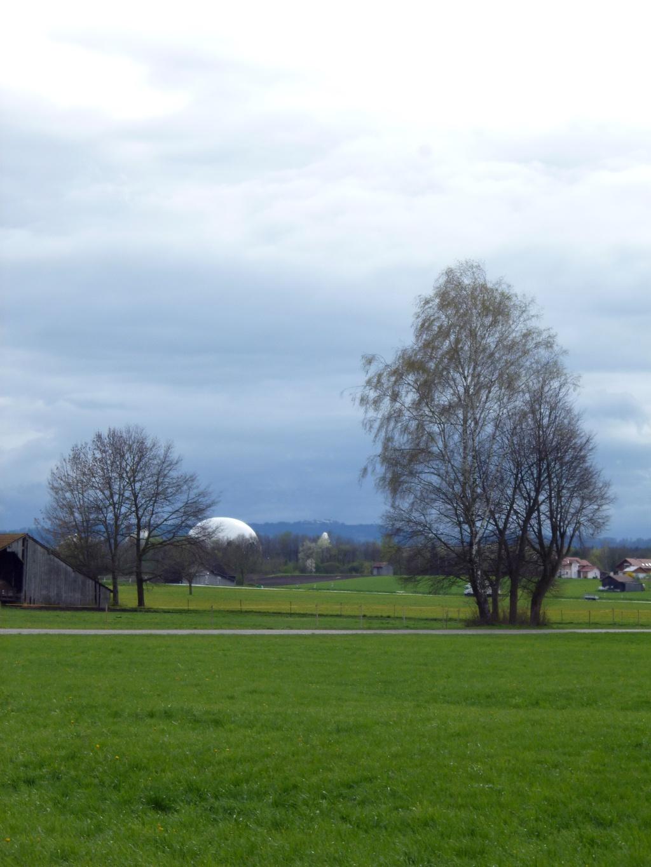 Blick vom Weg auf die große weiße Kugel des Industriedenkmals Radom Raisting auf dem Areal der Erdfunkstelle - dahinter die Alpen. (Monika Heindl)