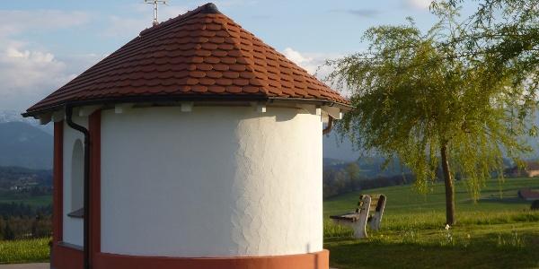 Die kleine Kapelle am östlichen Ortsrand von Schönberg steht direkt vor der eindrucksvollen Kulisse der Alpenkette.