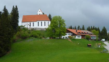 Die Kirche St. Georg und der wenig unterhalb gelegene Panorama-Gasthof auf dem Auerberg.