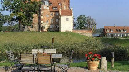 Von der Terrasse des Restaurants blickt man auf Schloss Ulrichshusen am gleichnamigen See.
