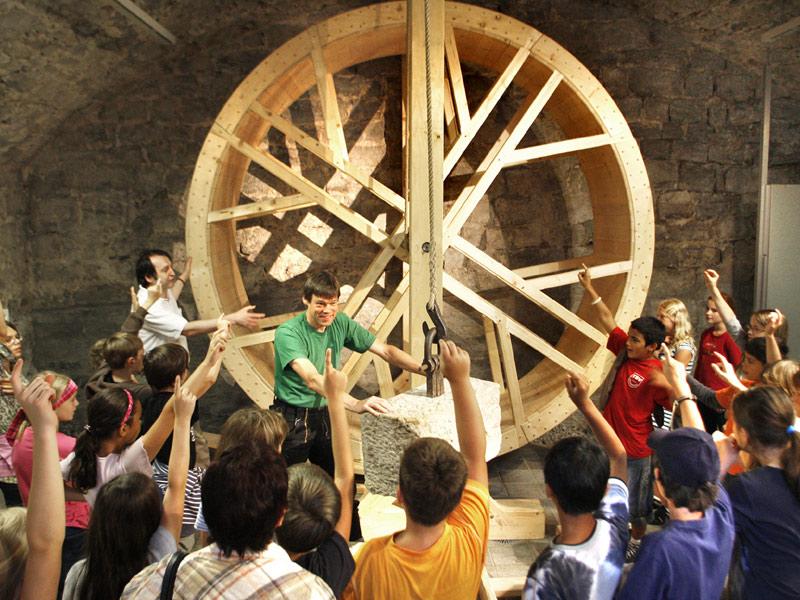 Funktionsfähiger Nachbau eines mittelalterlichen Tretradkrans. Mithilfe solcher Hebemaschinen konnten die Mitarbeiter einer Bauhütte schwere Lasten in große Höhen bringen.   - © Quelle: HFM