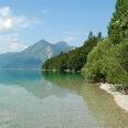 Glasklares Wasser, umgeben von Nadelbäumen und Bergen - der Walchensee.