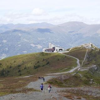Wirft man am Weg zum Wöllaner Nock einen Blick zurück zur Kaiserburg- Bergstation (2.039 m), erkennt man rechter Hand die Kalkfelsen des Kaiserburg-Gipfels (2.055 m). Links gibt der Verlauf des Bergrückens die Sicht auf im Tal gelegene Bauernhöfe frei. Von dort zieht sich im mittleren Bildhintergrund der sanft-hügelige Bergrücken von der Totelitzen (1.990 m) links nach rechts zu der alles überragenden Moschelitzen (2.310 m). Dahinter steigt der Horizont zum Klomnock auf 2.331 Meter Seehöhe an.