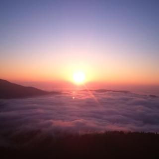 Sonnenaufgang kurz unterm Gipfelkreuz des Stubalpenspeiks. Aus dem Nebel taucht der Rappoldkogel (1928m)
