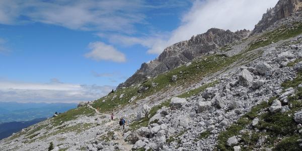 Das erste Wegstück führt über einen flachen Steinpfad in der Kulisse der Latemar-Türme.