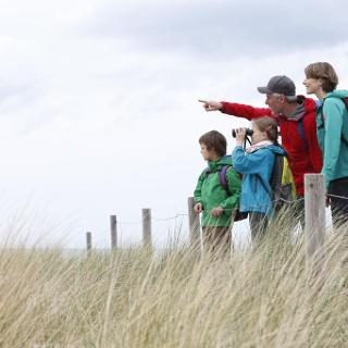 Familie blickt über die Dünen auf die Ostsee