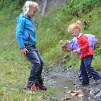 Kinder spielen mit selbst gebauten Schifferln