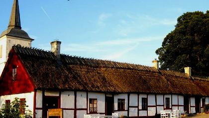 Gammal gård med kyrktornet i bakgrunden