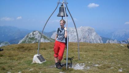 Glocke am Gipfel des Roßkofels mit dem mächtigen Kalkklotz des Trogkofels im Hintergrund