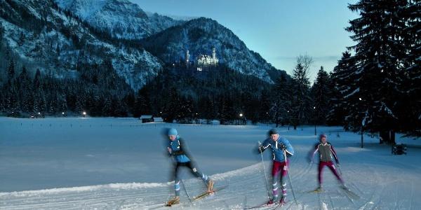 Flutlicht-Langlauf vor der Kulisse von Säuling und Schloß Neuschwanstein