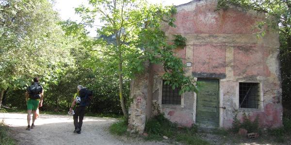 an einer alten Kirche vorbei, flach das Tal hinein
