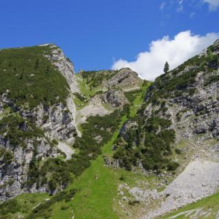 Entlang der steilen grasigen Rinne geht es bis oberhalb der mittleren Felsformation