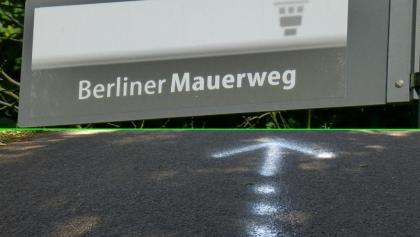 Mauerweg: Kennzeichnung mit Schild und meist auch mit weissem Pfeil am Boden
