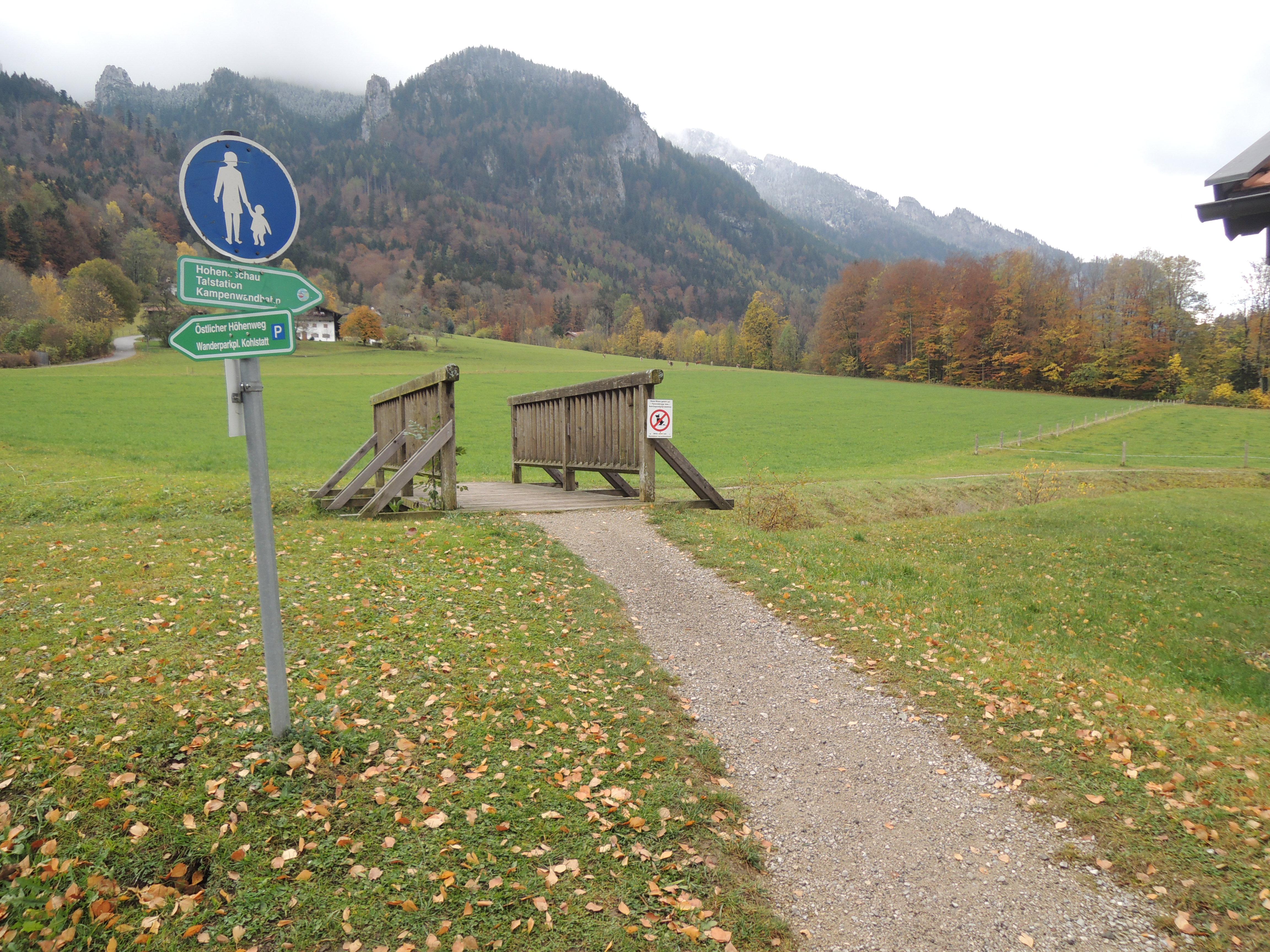 Brücke hinter einer Hofstelle mit Wegweiser zur Kampenwandseilbahn