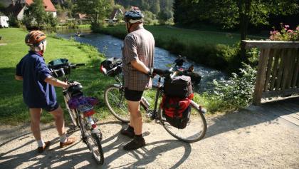 Radler am Fluss Pegnitz, Blick auf Felsen, Kanufahrer und Fachwerkhäuser