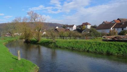 Blick auf das Dorf Buix mit dem Fluss L'Allaine.
