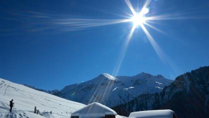 Verschneite Alpgebäude unter dem Dreispitz.