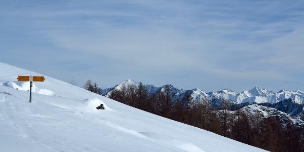 Eingeschneiter Wegweiser auf der Alpe Pesced.