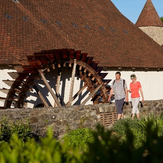 Wanderer beim Wasserrad Schloss Hallwyl (Etappe Schloss Hallwyl - Lenzburg)
