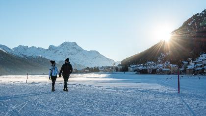 Winterwandern auf dem gefrorenen Champferersee mit Sonnenuntergang hinter Silvaplana