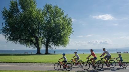 Familie fährt mit dem Velo durch den Seepark in Arbon.