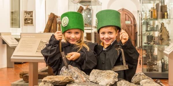 zwei Kinder in Bergbauuniform, an einem Erzhunt in der Bergbauausstellung des Stadt- und Bergbaumuseums Freiberg stehend