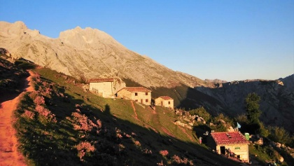 Die idyllisch gelegene Siedlung am Beginn des Zustieges leuchtet im Morgenrot.