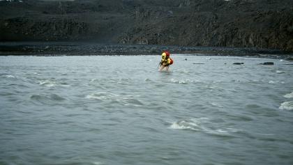 Mann durchquert den Fluss Svedjá im Hochland von Island