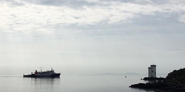 Carraig Fhada lighthouse and passing Calmac ferry to Kennacraig
