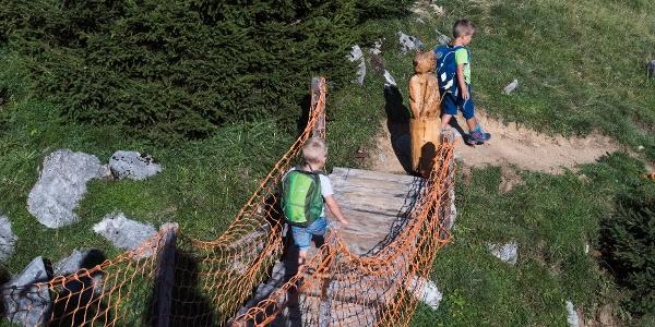 Kinder laufen über die Holz-Hängebrücke