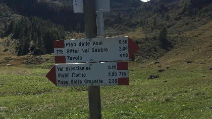 Wegweiser bei Mga. Val Bresciana sup. mit Blick auf Dosso Betti
