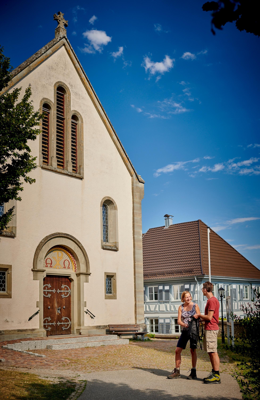 Wanderer vor der St. Ulrich-Kirche in Güttingen