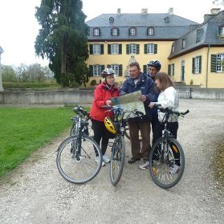 Radeln vor historischer Kulisse: ADFC-Tourenführer Thomas Bagdahn mit seiner Gruppe vor der Burg in Lüftelberg. Der barocke Bau aus dem 18. Jahrhundert steht auf der Überresten einer mittelalterlichen Burg.