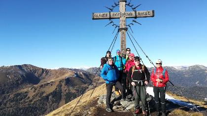 AV-Wanderer unter dem Schoberkreuz - im Hintergrund links der Kor- und Rinsennock - am Horizont die Ankogelgruppe mit der Hochalmspitze