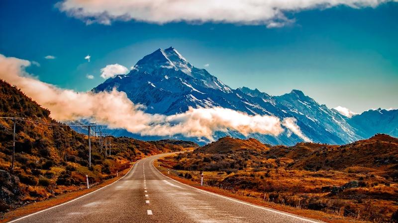 Straße durchs Mackenzie Country, im Hintergrund die verschneiten Südalpen