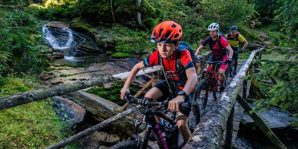 Mountainbiker fahren über eine Brücke