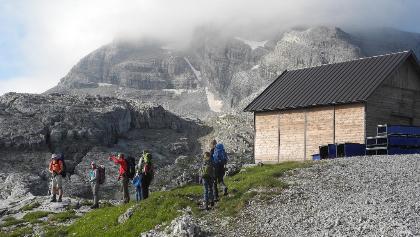 Cima Groste (Gipfel in Wolken) mit der Aufstiegsrouite (über dem linken Dachrand der Hütte)