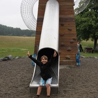 Kind rutscht vom Förderturm auf dem Waldspielplatz