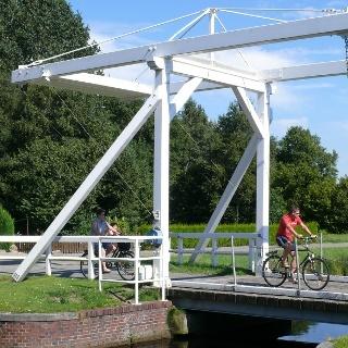 Radfahrer auf einer Fehnbrücke in Ostrhauderfehn