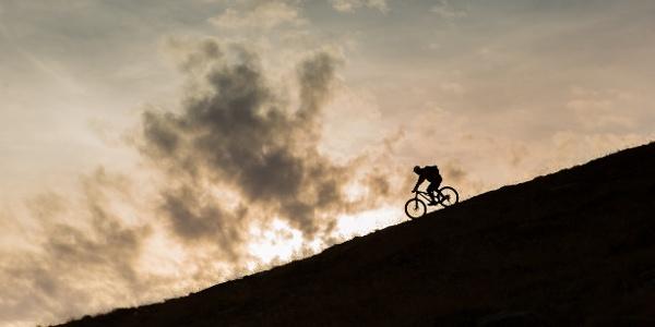 Person auf dem Mountainbike, die am Ende des Tages im Lötschental eine Piste hinunterfährt.