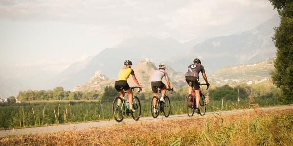 3 cyclistes sur la route avec les châteaux de Sion en arrière plan