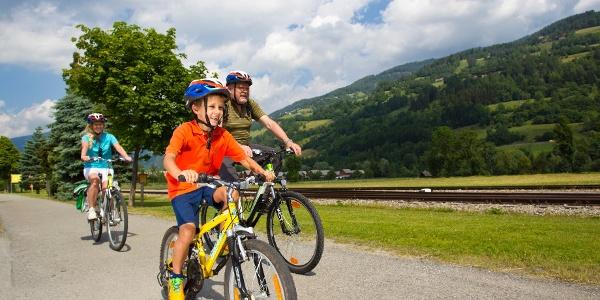 Radeln am Murradweg mit der Murtalbahn im Hintergrund