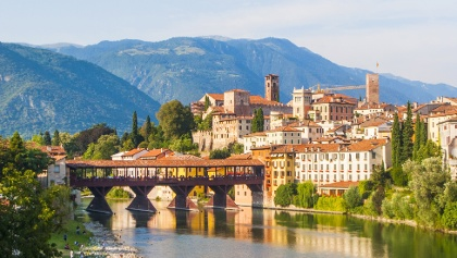 Old wooden bridge spans the River Brenta at the romantic village Basano del Grappa