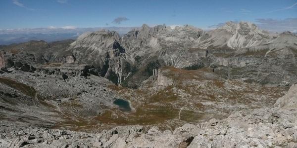 Der Crespeinasee, hier vom Sas Ciampac (2.670m) aus gesehen, liegt eingebettet in der Crespeina-Hochebene, deren Felswände dahinter steil ins Langental abfallen.