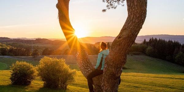 Frau genießt den Sonnenuntergang auf dem Kornberg bei Dillenburg