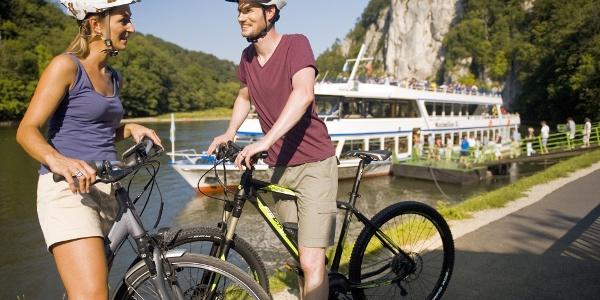 Radfahrer vor einem Schiff beim Kloster Weltenburg - Fahrräder können auf den Schiffen mitgenommen werden.
