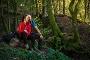 Zwei Rothaarsteig-Wanderer sitzen im grünen Wald auf einem Stein