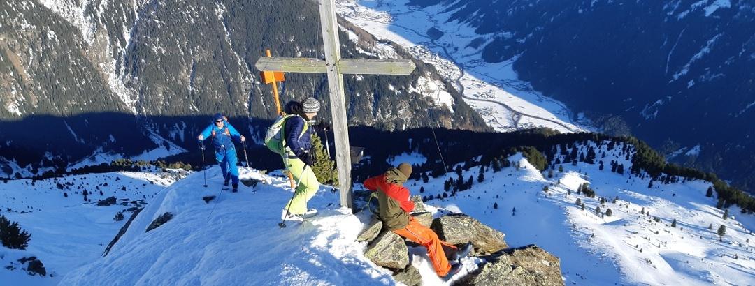 Gipfelkreuz der Seblasspitze (Wintergipfel), unten Neustift im Stubaital.